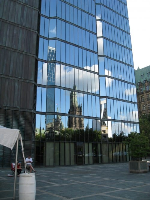 Reflection of surrounding context in custom design bronze and reflective glass curtain wall along east elevation